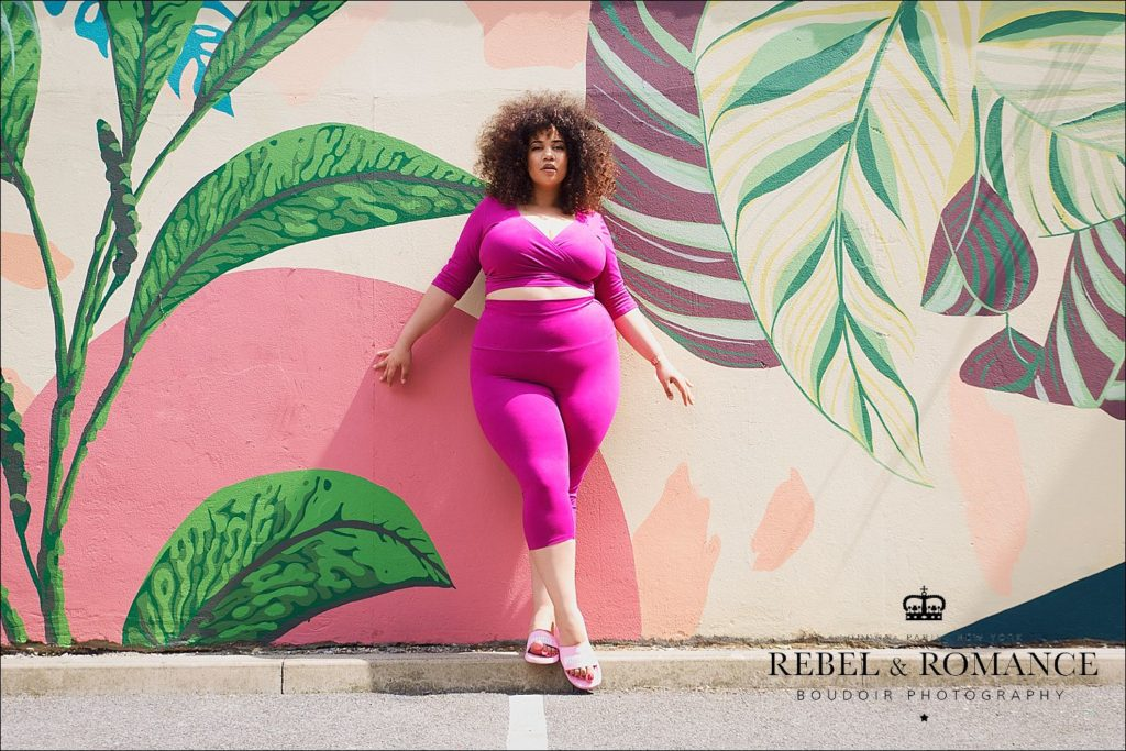 tropical photo shoot of plus size woman with afro wearing pink