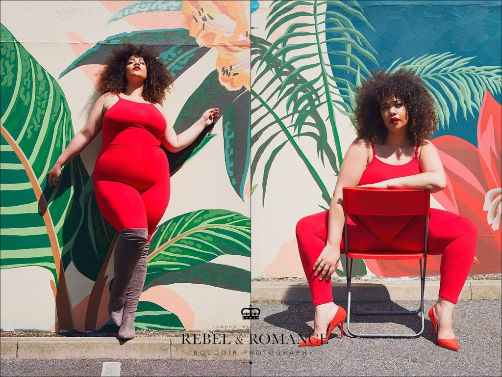 plus size woman in red posing in front of a tropical wall mural
